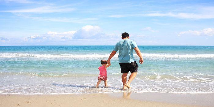 Vater und Kind gehen am Strand spazieren