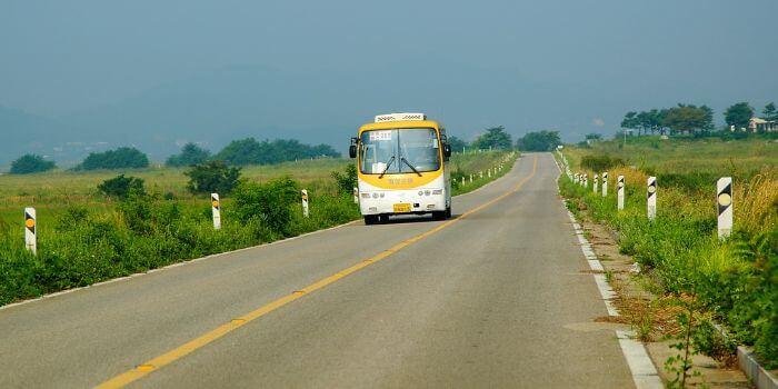 ein Reisebus fährt auf einer Straße mit grünen Wiesen links und rechts