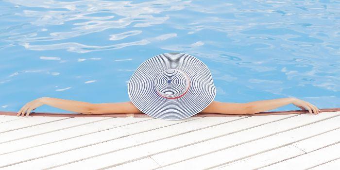 eine Frau mit einem Sonnenhut liegt im Pool