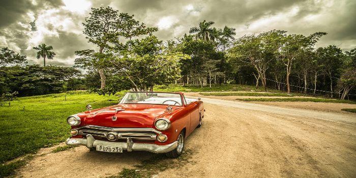 ein Oldtimer Cabrio steht am Straßenrand und dahinter ein Wald