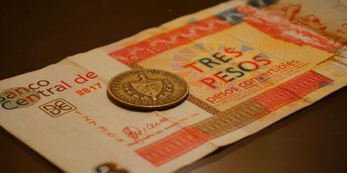 eine Peso Münze liegt auf einem Peso Geldschein