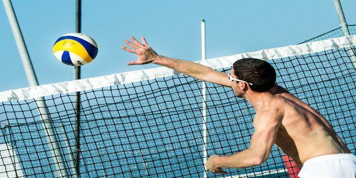 Ein Mann schlägt einen Volleyball übers Netz