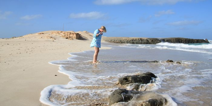 Eine Frau steht im Meer an einem Sandstrand in Kap Verde