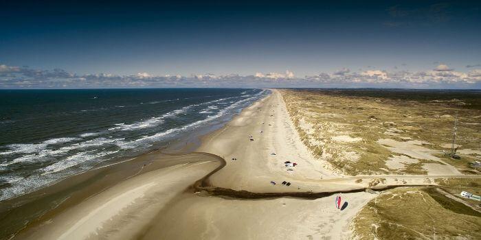 Das Bild zeigt einen langen Strandabschnitt an der Nordsee mit starkem Wellengang