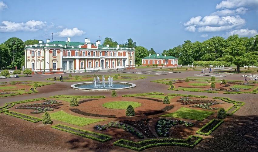 Gut restauriertes Schloss mit aufwendig angelegtem Garten davor.