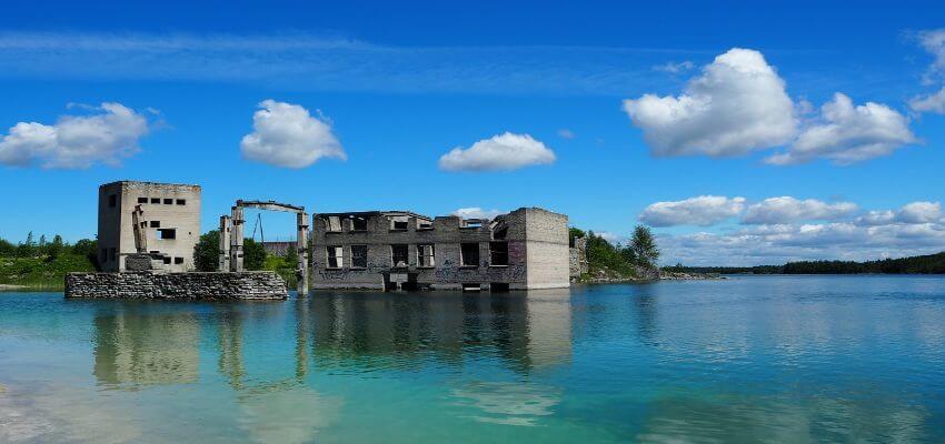 Ein verfallenes Gebäude steht neben und in einem See.