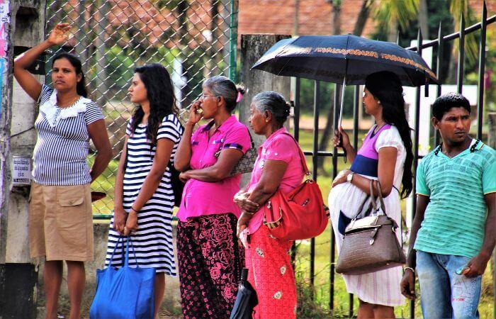 Menschen stehen am Straßenrand von Sri Lanka und warten auf den Bus