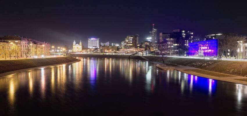 Ein Fluss wo links und rechts beleuchtete Gebäude stehen