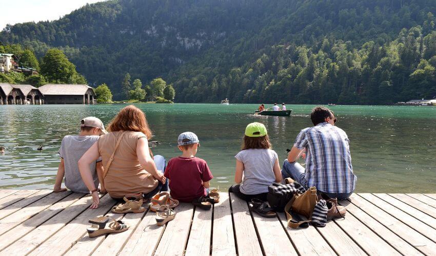 Eine Familie mit 3 Kindern sitzt am Steg eines Sees.