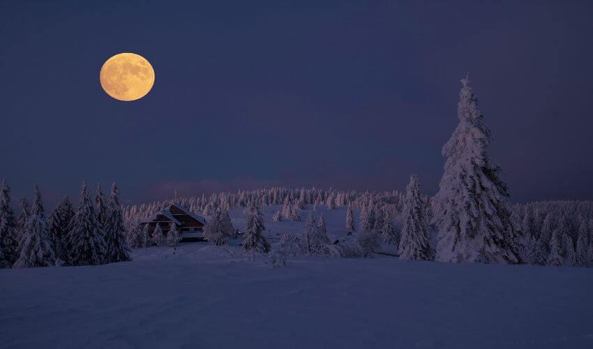 Vollmond über eine beschneite Winterlandschaft.