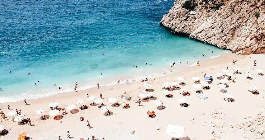 Schöner Sandstrand wo gerade viele Urlauber am baden sind.