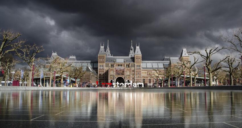 Das Rijksmuseum von außen fotografiert mit, wobei schwarze Gewitterwolken über das Museum ziehen.