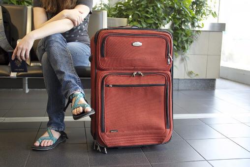 Eine Frau wartet mit einem braunen Koffer am Flughafen auf den Flug