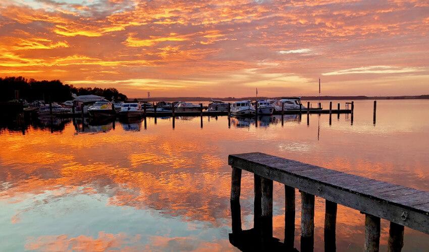Ein Bootssteg wo einige Boote befestigt sind und im Hintergrund eine orangerote Abenddämmerung.