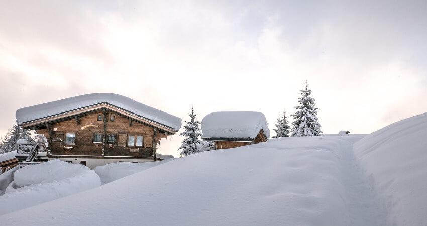 Ein Holzhaus mit viel Schnee auf dem Dach.