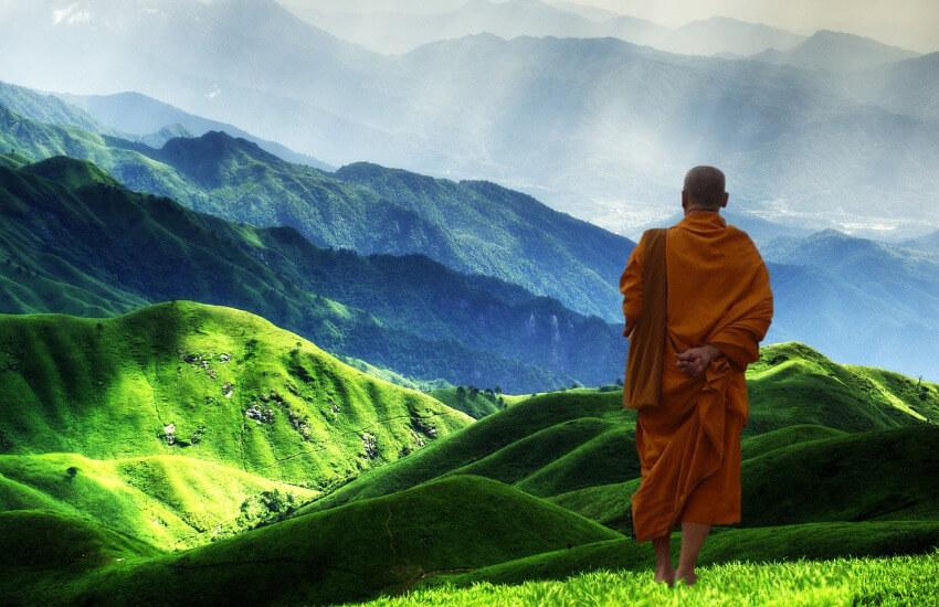 Ein Mönch steht auf einem Hügel und blickt über einen grün bewachsenen Berg.