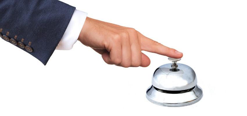 Ein Finger eines Mannes welcher auf eine Rezeptionsglocke drückt.