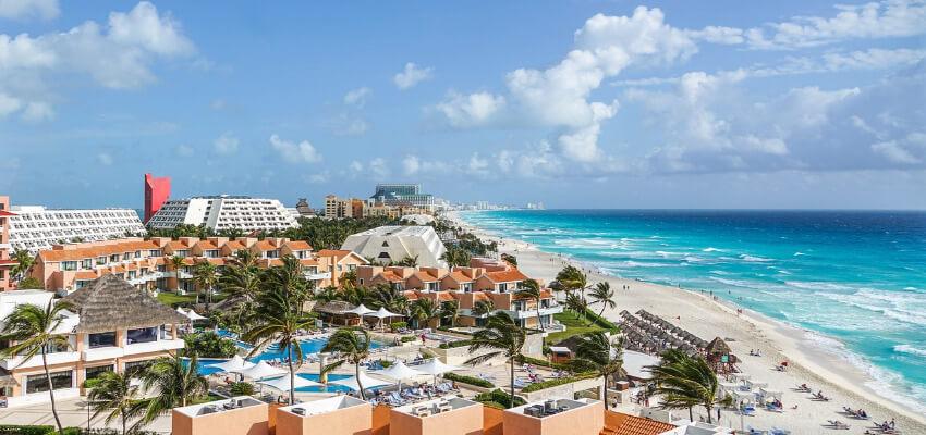 Ein Resort in Cancun bestehend aus mehreren Gebäuden direkt an einem langen Sandstrand.