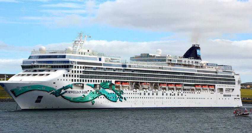Ein mittelgroßes Kreuzfahrtschiff ankert an der Küste.