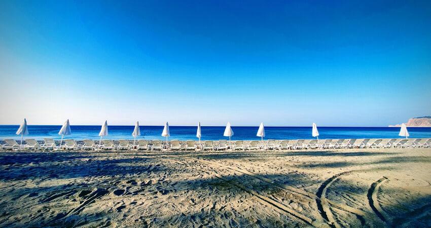Ein breiter Sandstrand mit liegen und Sonnenschirmen unter blauem Himmel.