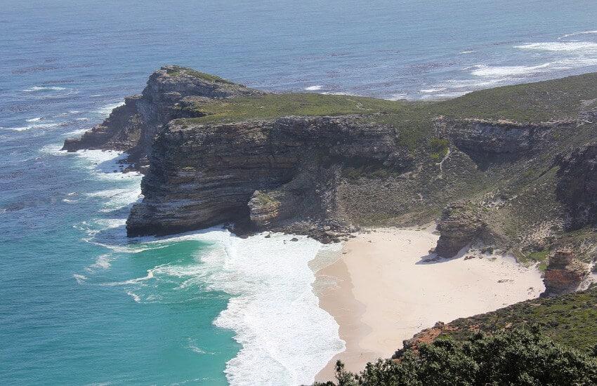 Eine hohe steile Felsklippe, dazwischen ein kleiner flacher Sandstrand.
