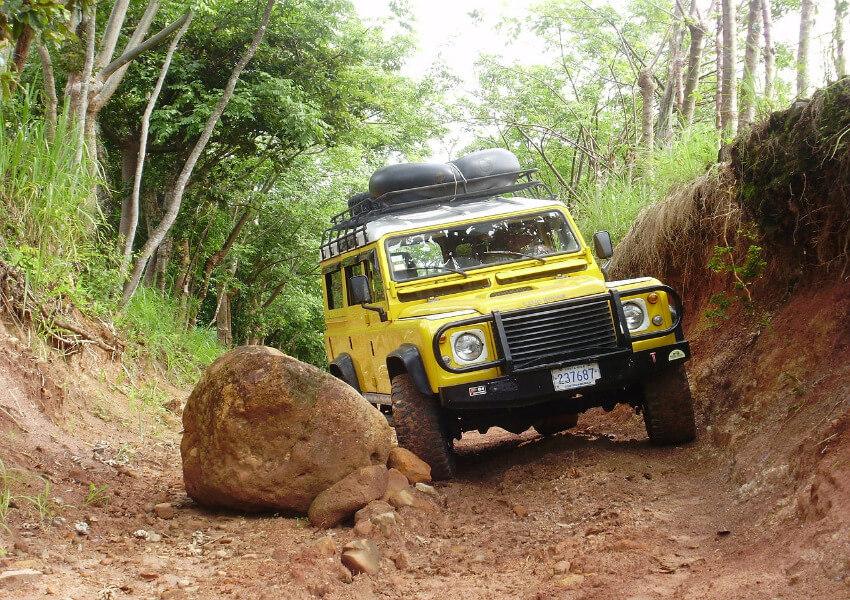 Ein gelber Geländewagen auf einer Schotterpiste unterwegs, wobei einem großen Stein ausgewichen werden muss, der auf den Weg gefallen ist.