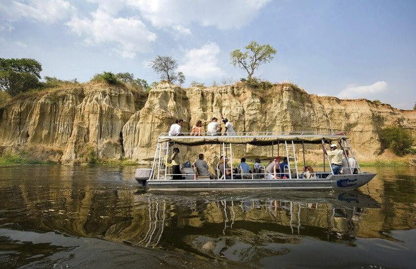Ein Boot mit 15-20 Touristen unterwegs auf einen Fluss im Murchison Nationalpark.