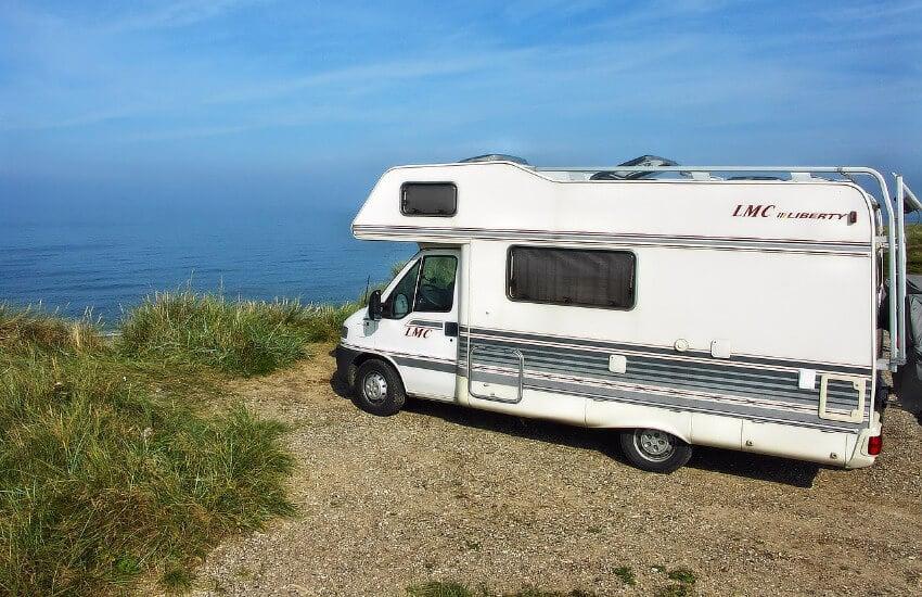 Ein Wohnmobil parkt alleine an einem abgelegenen Platz am Meer.