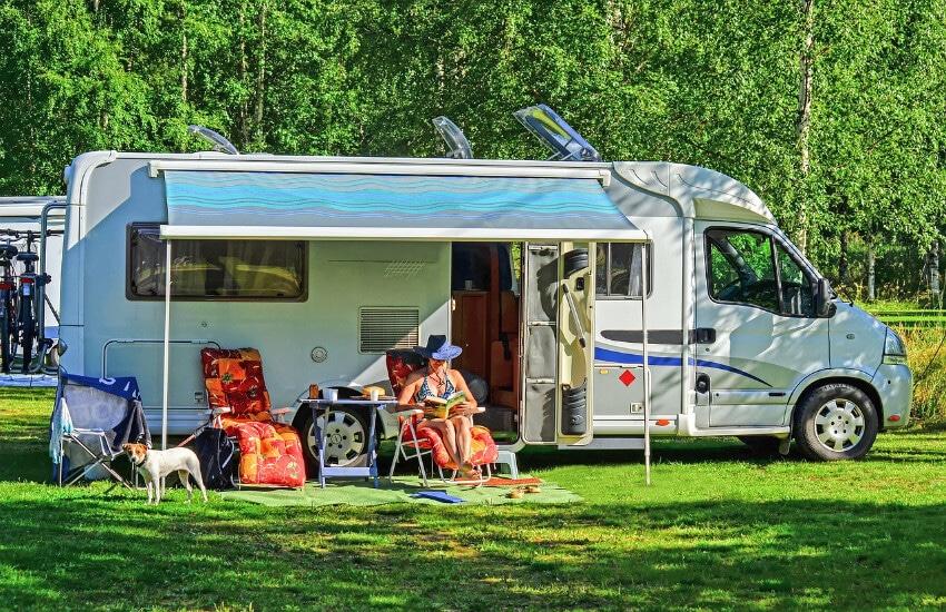 Ein Wohnmobil parkt an einem Campingplatz mit einem kleinen Vordach. Davor eine Frau im Stuhl und list ein Buch.