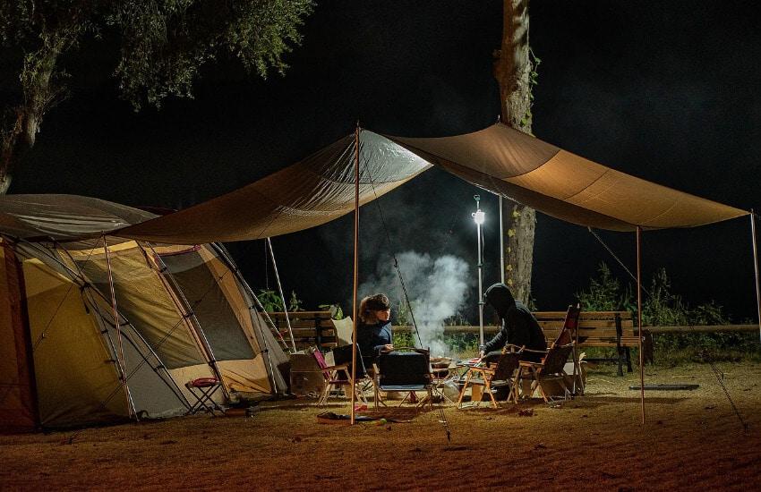 Zwei Männer sitzen bei Nacht neben Ihrem Zelt unter einem Vordach und grillen.
