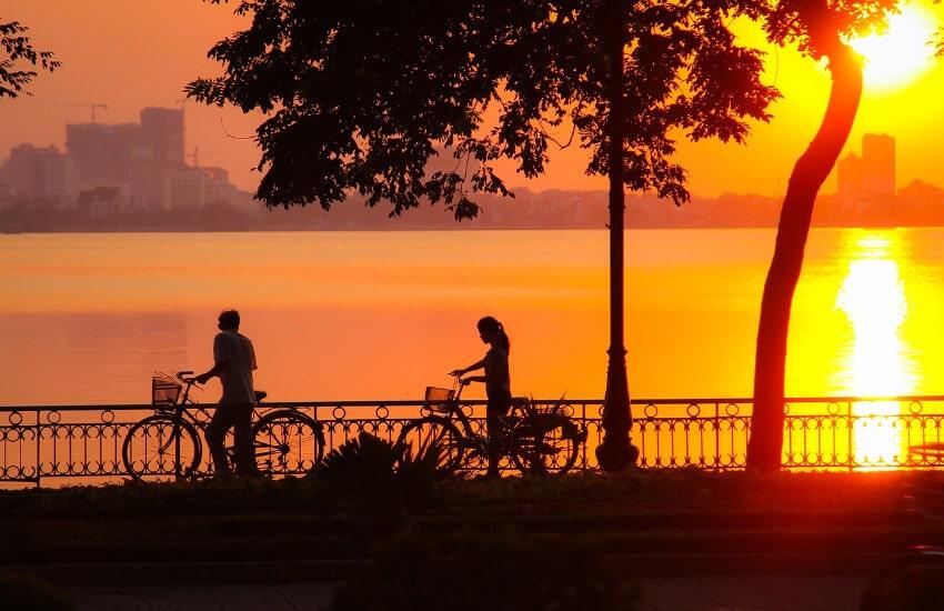 Zwei Radfahrer schieben Ihr Rad entlang eines Sees bei Sonnenuntergang.