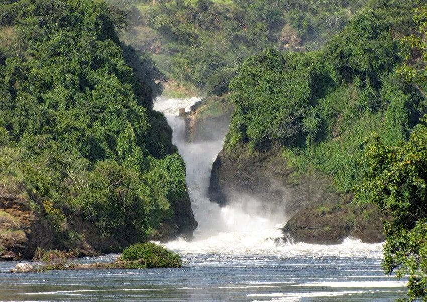 Ein schmaler Wasserfall zwischen mit Sträuchern bewachsenen Klippen.