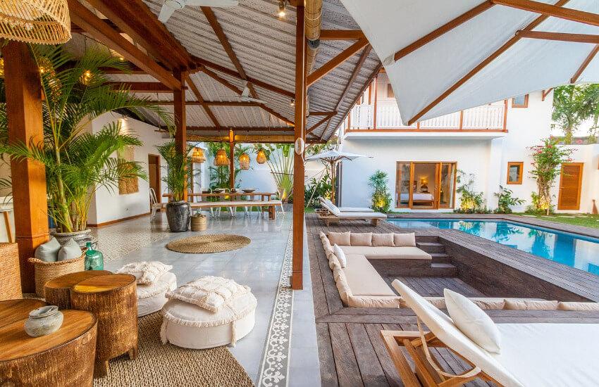 Eine Luxusimmobilie mit überdachter Terrasse und einem Pool im Garten.