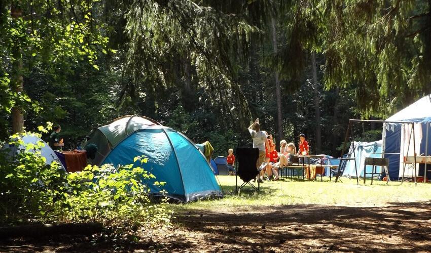 Familien sitzen auf einer Klappgarnitur zwischen Zelten.