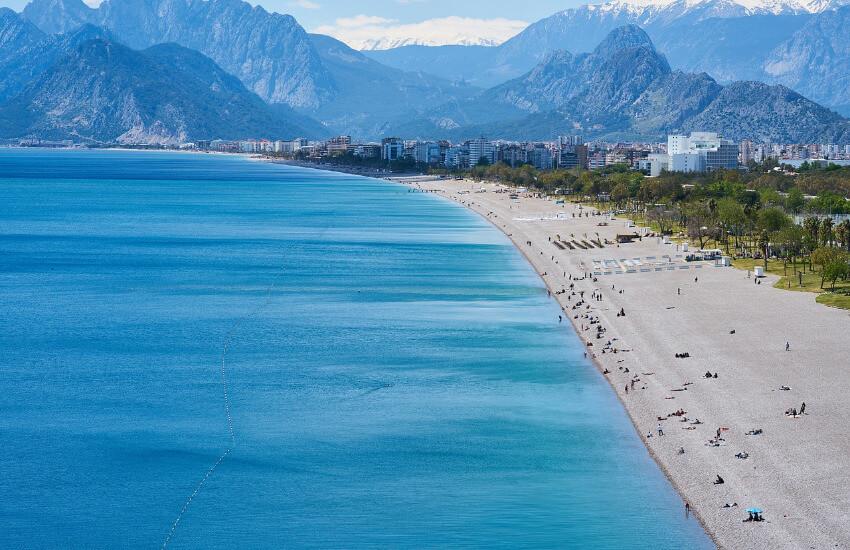 Ein langer Streifen Sandstrand entlang vom blauen Meer.